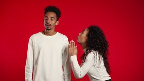 Cute african young woman begging her boyfriend or husband about something over red background.