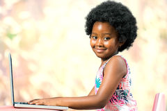 Cute afro american kid typing on laptop. Royalty Free Stock Photos