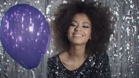 Cute afro american woman with balloon blowing confetti over shiny background.