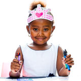 Cute afro girl holding wax crayons. Royalty Free Stock Photo
