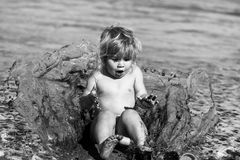 Cute amazed baby boy made big mud splash of water. Childhood. Childhood. Cute amazed baby boy with blond hair made big mud splash of water and sand on sunny royalty free stock photo