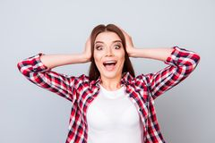 Cute amazed brunette girl in shirt, holding her head, she is sho. Cked, extremely happy, with wide open eyes and mouth on pure background Stock Photos