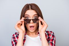 Cute amazed brunette girl tourist in shirt, holding her trendy g. Lasses, she is shocked, with wide open eyes and mouth on pure background Stock Photography