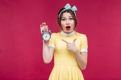 Cute amazed pinup girl pointing on alarm clock Stock Image