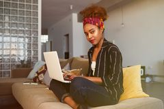 Cute american african female blogger working remotely on digital netbook with internet text. African woman copywriter. Typing article for website on keyboard of royalty free stock photography