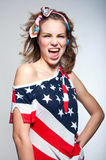Cute American girl. Studio portrait of young patriotic American girl wearing bright makeup, casual clothes like colorful head band and off the shoulder top tank Royalty Free Stock Image