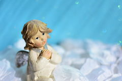 Cute angel. On the fluffy white leaves and with shiny light blue background stock photography