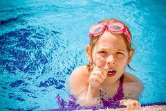 Cute Angry Little Girl Playing in Swimming Pool royalty free stock image