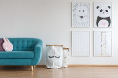 Cute animal posters. Hanging on white wall near a turquoise couch in white interior of baby room Stock Images