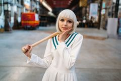 Cute anime style blonde girl with baseball bat. Cosplay fashion, asian culture, doll in dress, woman with makeup in the factory shop royalty free stock photo