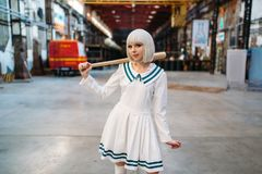 Cute anime style blonde girl with baseball bat. Cosplay fashion, asian culture, doll in dress, sexy woman with makeup in the factory shop stock photography
