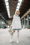 Cute anime style blonde woman with toy bear. In hand. Cosplay, japanese culture, doll in dress on abandoned factory royalty free stock photos