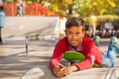 Cute Arabian boy laying on green skateboard Royalty Free Stock Image