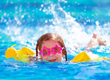 Cute arabic girl in the pool. Closeup portrait of cute little arabic girl swimming in the pool, happy child having fun in water, beach resort, summer vacation Stock Images