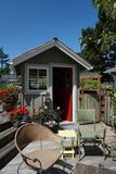 Cute artist`s she-shed on a deck with flowers and patio chairs. Colorful red door and geranium planters stock images