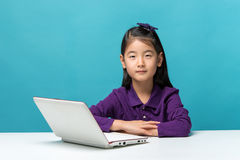 Cute asia little girl who enjoy the laptop computer on blue back Royalty Free Stock Photo