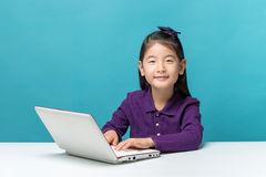 Cute asia little girl who enjoy the laptop computer on blue background Royalty Free Stock Photo