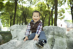 Cute asian baby boy sitting on a rock. In a park Royalty Free Stock Photos