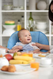 Cute Asian baby at Dining Table with family. Portrait of adorable Asian baby boy smiling, sitting in little chair with family at dining table during breakfast Stock Photos