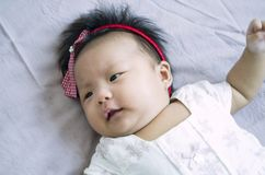 Angry Baby girl. Cute Asian baby girl on the blanket background Royalty Free Stock Photo