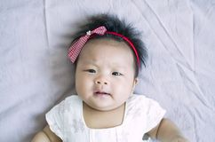 Angry Baby girl. Cute Asian baby girl on the blanket background Stock Photos