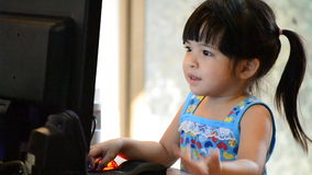 Cute asian baby girl playing computer