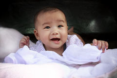 Cute Asian baby smiling face lied on bed Stock Photo