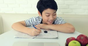 Cute asian boy doing homework at home with smile face. stock video footage