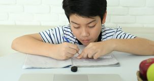 Cute asian boy doing homework at home with smile face. stock video