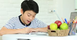 Cute asian boy doing homework at home with smile face. stock footage