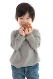 Cute asian boy eating cream puff stock photos