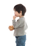 Cute asian boy eating cream puff Stock Images