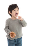 Cute asian boy eating cream puff Royalty Free Stock Photography