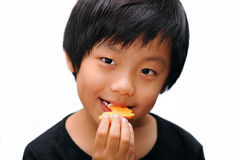 Cute Asian boy enjoying a cookie Royalty Free Stock Photo