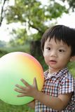 Cute Asian boy holding a ball Royalty Free Stock Images