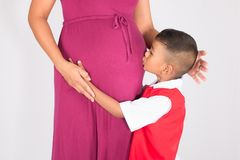 Cute asian boy kiss belly mom. On white background Stock Photos