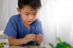 Cute asian boy is playing with blocks from toy constructor with. Copy space. Educational toys concept stock images
