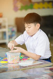 Cute asian boy playing with plastic blocks in class room at scho Royalty Free Stock Images
