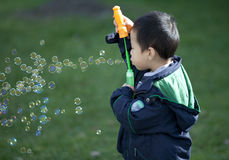 Cute asian boy playing with soap bubbles outdoor Stock Photos
