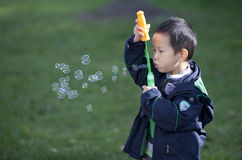 Cute asian boy playing with soap bubbles outdoor Royalty Free Stock Photography