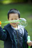 Cute asian boy playing with soap bubbles outdoor Royalty Free Stock Photo