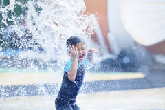 Cute asian boy playing at water park. Asian boy having fun with pool fountain shot duing summer time Stock Photos