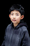 Cute Asian Boy Posing on Black Background in Studio. Cute handsome Asian boy posing in studio on black background with backlit effect royalty free stock images