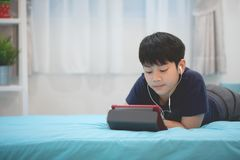 Cute asian boy rest on bed and hand holding tablet computer. Cute asian boy rest on bed and hand is holding tablet computer Stock Photo