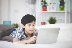 Cute asian boy rest on bed and typing laptop computer. Cute asian boy rest on bed and is typing laptop computer Royalty Free Stock Photos