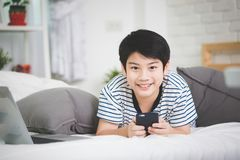Cute asian boy rest on bed and using smart cell phone with smile. Face Stock Photo