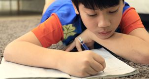 Cute asian boy rest on floor and doing homework at home with smile face stock footage