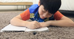 Cute asian boy rest on floor and doing homework at home with smile face stock video