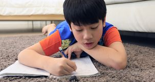 Cute asian boy rest on floor and doing homework at home with smile face stock video footage