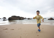 Cute asian boy running on beach Stock Photo